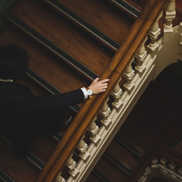 Picture of man in suit walking up staircase