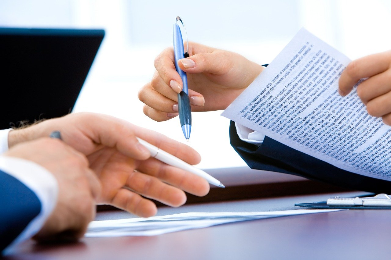 Picture of hands and documents on a table with a person holding documents and a pen